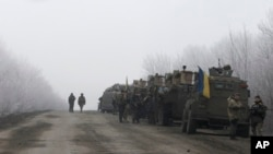 FILE - Ukrainian military convoy stops between the towns of Dabeltseve and Artemivsk, Feb. 14, 2015.
