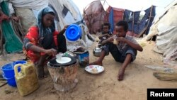 "An internally displaced Somali girl prepares the traditional Somali breakfast ""Anjero"" at Sayyidka camp in the Howlwadag district, south of Somalia's capital Mogadishu, May 3, 2013."