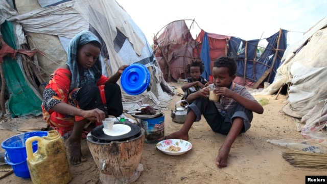 "An internally displaced Somali girl prepares the traditional Somali breakfast ""Anjero"" at Sayyidka camp in the Howlwadag district, south of Somalia's capital Mogadishu, May 3, 2013."