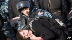 Arhia - Pripadnik ruske policije privodi demonstranta u Moskvi, 26. marta 2017.