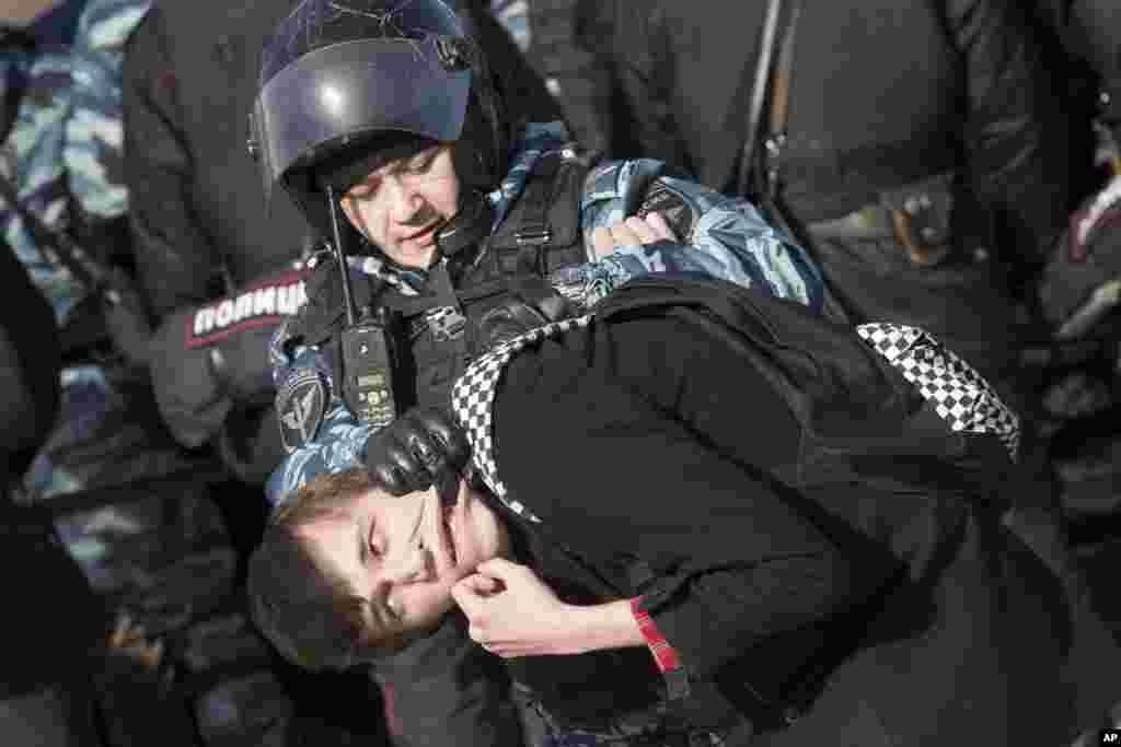 Police detain a protester in downtown Moscow, Russia. Thousands of people crowded into Moscow's Pushkin Square for an unsanctioned protest against the government.