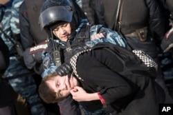 FILE - Police detain a protester in downtown Moscow, Russia, March 26, 2017. The threat of a rising protest movement in Russia has been a driving force behind the creation of patriotic programs for young people.