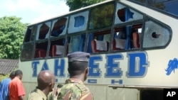 A Kenyan police officer with civilians views a Taheed Bus at the Lamu Police Station in Lamu, July 19, 2014.