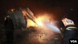 一名巴勒斯坦 消防队员星期六一早在以色列空袭加沙市后扑灭一建筑物上的大火