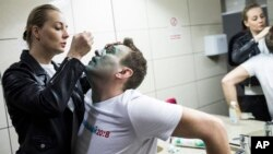 Yulia, wife of Russian opposition figure Alexei Navalny, treats him after unknown attackers doused him with a green chemical solution outside a conference venue in Moscow, Russia, April 27, 2017.