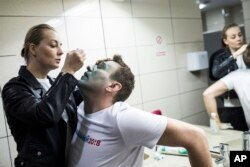 FILE - Yulia, wife of Russian opposition leader Alexei Navalny, treats him after unknown attackers doused him with green antiseptic outside a conference venue in Moscow, Russia, April 27, 2017.