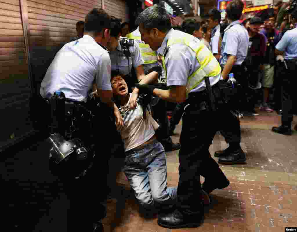 A passerby frightened by police action is helped up at Mongkok shopping district in Hong Kong. Hong Kong police cleared one of the largest protest sites, arresting scores of pro-democracy activists.