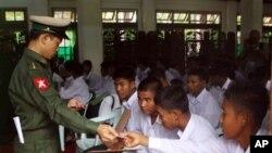برمی فوج کا ایک اہلکار بچوں کی رہائی سے قبل اُنھیں شناختی دستاویزات دے رہا ہے۔ (فائل فوٹو)