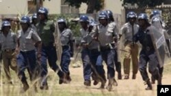 FILE: Police leave a scene after throwing teargas at a house in Chitungwiza, Zimbabwe, Sunday, Nov. 6, 2011.