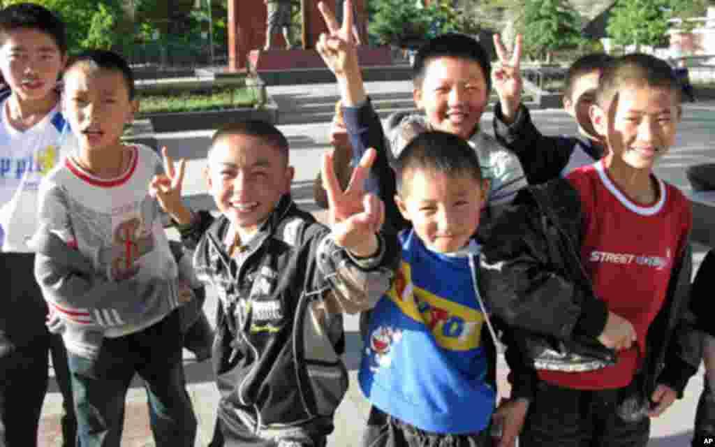 在会师广场上玩耍的学童摆出胜利的姿势