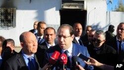 Firayim ministan Tunisiya, Youssef Chahed, yana magana da 'yan jarida a lokacin da ya ziyarci wani caji ofis da aka kai ma hari a El Battan, kilomita 35 a yamma da Tunis
