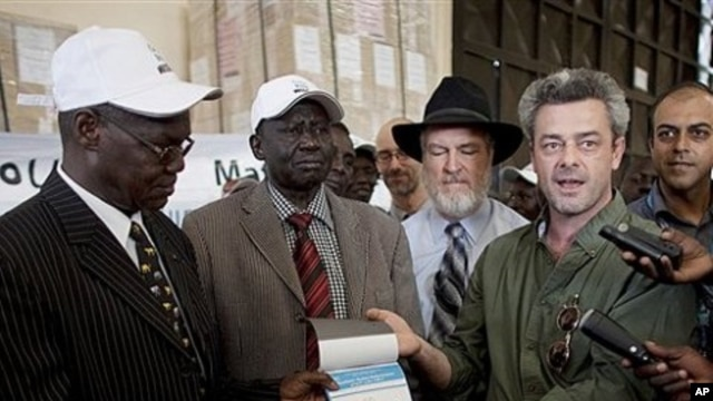 Eamon Omordha, right, Deputy Director of United Nations Integrated Referendum and Electoral Division, hands over a referendum ballot to Justice Chan Reec Madut, left, Chairman of the Southern Sudan Referendum Bureau, during a material handover ceremony in