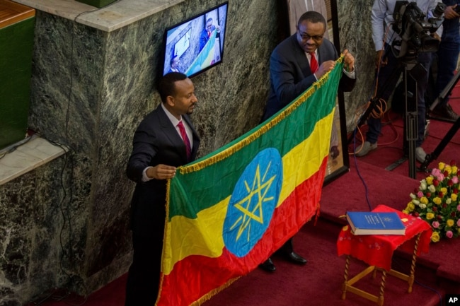 The outgoing prime minister, Haileamariam Dessalegn, who symbolically resigned from his post, hands over the Ethiopian flag to Abiye Ahmed, left, April 2, 2018.