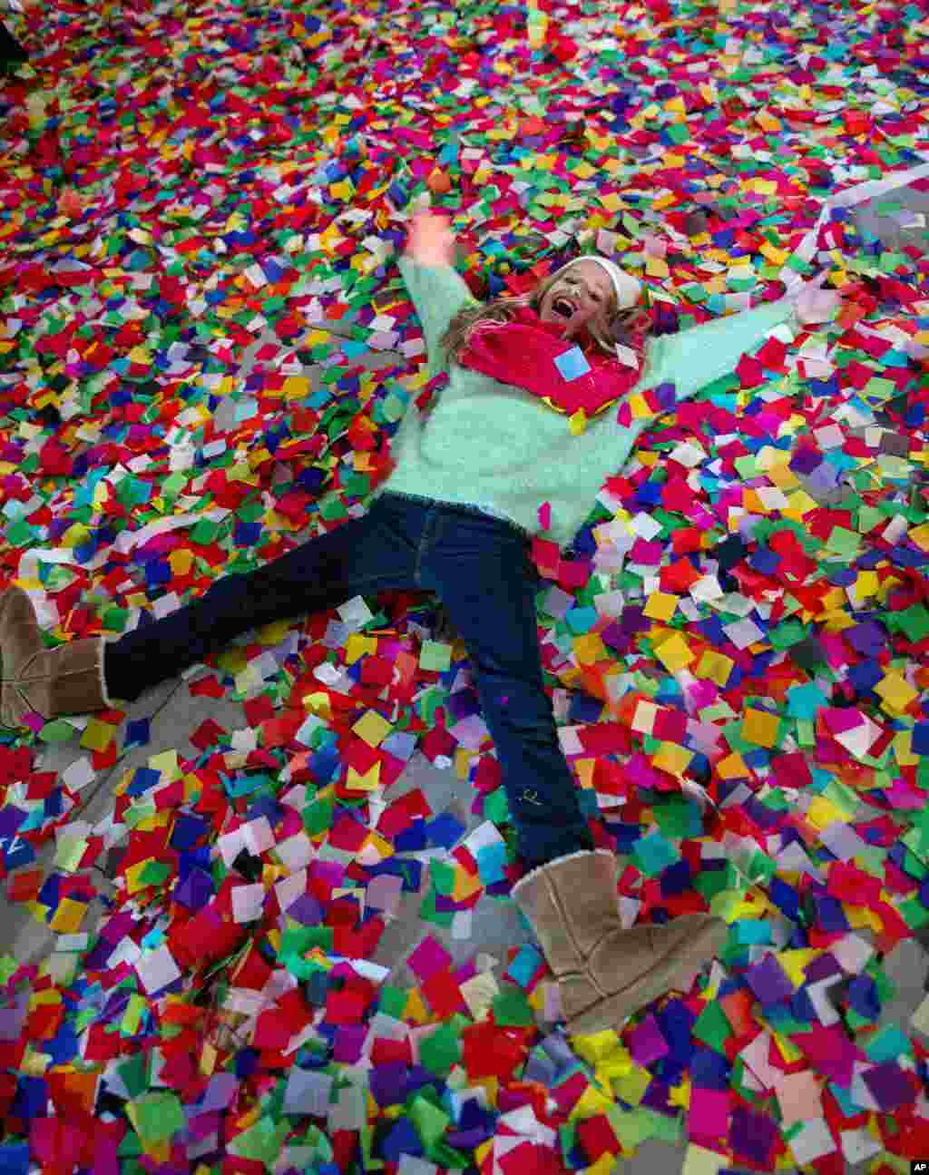 Nicole Tacher, 11, lays in confetti on a hotel balcony as the new year is celebrated, Times Square, New York City, New York, Jan. 1, 2014.