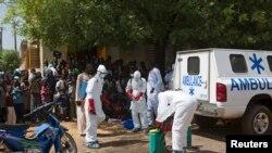 Des agents de santé se revêtant de leurs équipements individuels de protection, afin de désinfecter une mosquée, à Bamako, au Mali, le 14 novembre 2014.