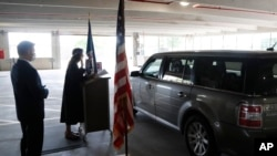 In this Friday, June 26, 2020 photo, U.S. District Judge Laurie Michelson, center, administers the Oath of Citizenship during a drive-thru naturalization service in a parking structure at the U.S. Citizenship and Immigration Services office.