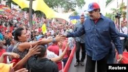 El mandatario venezolano saluda a partidarios durante un acto en apoyo del programa de viviendas del gobierno en el Palacio de Miraflores, en Caracas, el miércoles, 11 de mayo 2016.