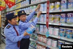 FILE - Chinese commercial law enforcement personnel inspect milk powder products at a supermarket in Lianyungang, Jiangsu province, China.