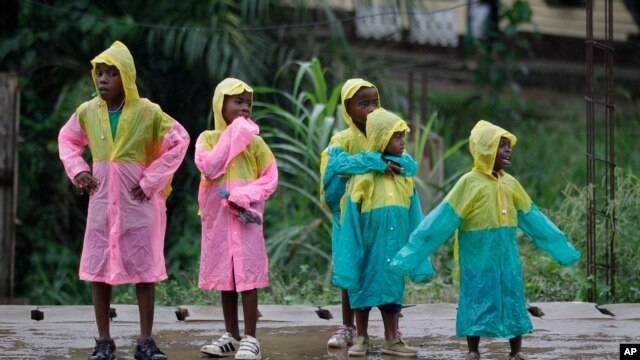 Girls wear matching raincoats as they wait along a roadside during a rain shower in Bata, Equatorial Guinea, (File photo).
