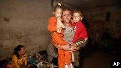 FILE - A local resident holds his children in a basement which is being used as a shelter following shelling in Donetsk, eastern Ukraine.