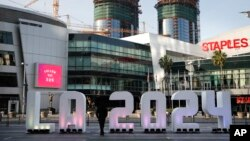 "FILE - A Los Angeles 2024 sign stands in front of Staples Center, in Los Angeles, May 11, 2017. An International Olympic Committee panel has praised Los Angeles and Paris for ""outstanding"" plans to host the 2024 Summer Games."