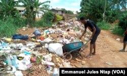 Des tas d'ordures barrent la route au lieu dit, derrière l'office du baccalauréat. Pas de bacs à ordures ici pour une forte population du quartier, à Yaoundé, au Cameroun, le 23 mai 2017. (VOA/Emmanuel Jules Ntap)
