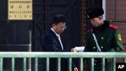 지난 2012년 중국 베이징 주재 북한대사관 입구에서 대사관 관계자가 경비를 서는 중국 공안원과 대화하고 있다. (자료사진)