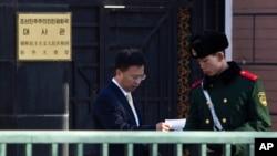 지난 2012년 2월 중국 베이징 주재 북한대사관 입구에서 대사관 관계자가 경비를 서는 중국 공안원과 대화하고 있다. (자료사진)