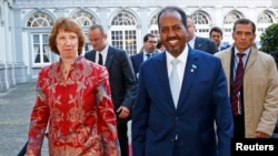 "Catherine Ashton and Somali's President Hassan Sheikh Mohamud arrive at a conference called ""New Deal in Somalia"" in Brussels. (September 2013.)"