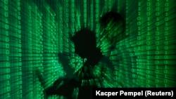 Foto ilustrasi memperlihatkan kode biner diproyeksikan pada seorang pria yang memegang komputer laptop, di sebuah kantor di Warsawa (foto: dok).