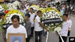 Cambodian labor union workers carry flowers as they march to mark the 7th year anniversary of Chea Vichea's death, Cambodia's former free trade union president.
