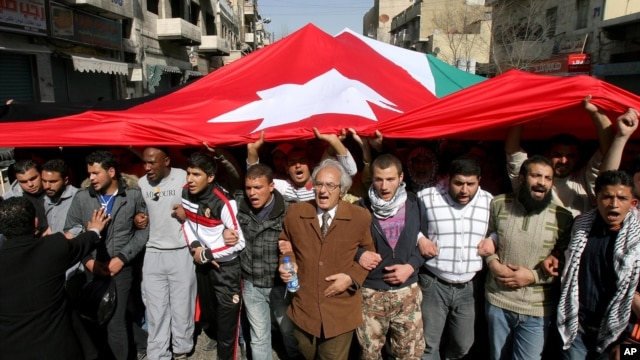 Jordanian supporters of the Islamic Action Front carry a giant Jordanian flag as they demand for political reforms during a protest in Amman, March, 4, 2011.