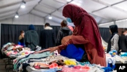 FILE - Afghan refugees pick out clothes at an Afghan refugee camp at Joint Base McGuire Dix Lakehurst, N.J., Sept. 27, 2021. The camp currently holds approximately 9,400 Afghan refugees and has a capacity to hold up to 13,000.