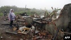 Bà Nguyễn Thị Thương, vợ của ông Đoàn Văn Vươn, đứng trước đống đổ nát của căn nhà bị chính quyền địa phương và các lực lượng vũ trang phá hủy, ngày 4/2/2012. Gia đình ông Vươn có 6 người bị truy tố và nhà cửa của họ bị phá hủy hoàn toàn.