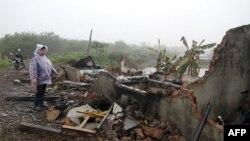 Vợ của ông Đoàn Văn Vươn, bà Nguyễn Thị Thương, đứng cạnh đống gạch đá đổ nát của căn nhà đã bị chính quyền và lực lượng võ trang phá hủy, 4/2/2012