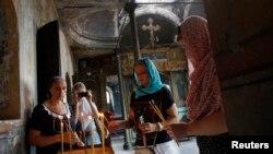 Anggota jemaat Rusia Ortodoks menyalakan lilin di Gereja St. Elijah di Istanbul (2/8). (Reuters/Murad Sezer)