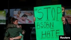 People grieve while Jesus Estrella, 21 holds a sign outside Young's Asian Massage