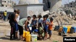 Des enfants collectent de l'eau après cinq jours de trève à Khan Younis dans le sud de la bande de Gaza, le 14 août 2014.