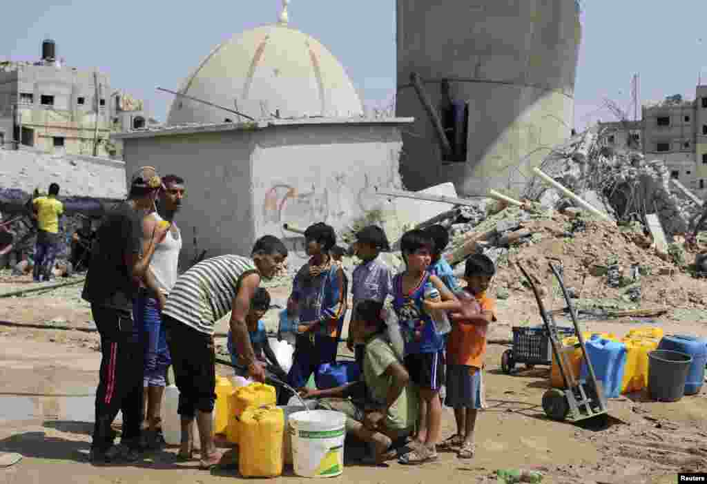 Children collect water during a five days truce in Khan Younis in the southern Gaza Strip, Aug. 14, 2014.