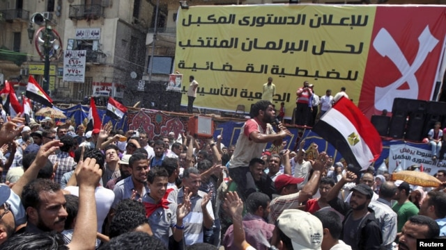 Supporters of Egyptian President-elect Mohamed Morsi rally in front of a banner rejecting recent military edicts at Tahrir square in Cairo, June 26, 2012.