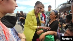 United Nations Under-Secretary General for Humanitarian Affairs, Valerie Amos (C), speaks to typhoon survivors at the airport in Tacloban, central Philippines, Nov. 13, 2013.