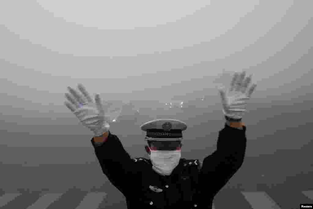 A traffic police officer signals to drivers during a smoggy day in Harbin, China, Oct. 21, 2013.