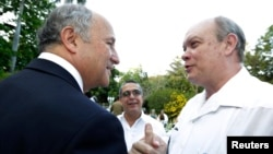 France's Foreign Minister Laurent Fabius (L) talks to Cuba's Minister of Foreign Trade and Commerce Rodrigo Malmierca Diaz (R) after a news conference in Havana, April 12, 2014.