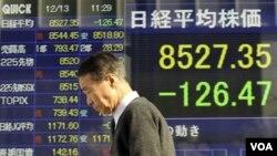 Seorang warga melintasi papan bursa di depan sebuah perusahaan sekuritas di Tokyo, Jepang. Pemerintah Jepang menurunkan prediksi pertumbuhan ekonomi untuk tahun fiskal sekarang ini karena kemerosotan ekonomi global (Foto: dok).