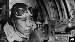 File photo shows Sgt. Gilbert Eagle Feather, Lakota from Rosebud, S.D., at the waist gun of his B-17 Flying Fortress, Dec. 24, 1943.