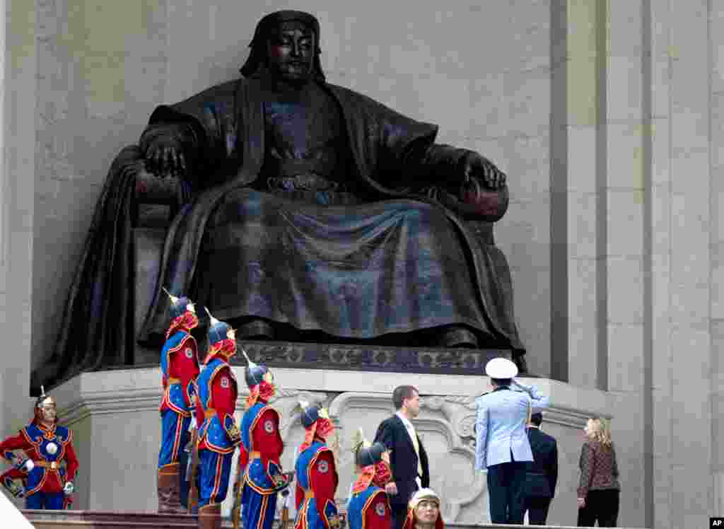 Clinton, right, under a statue of Chenggis Khan during her arrival ceremony at the Parliament House in Ulaanbaatar, Mongolia, July 9, 2012.