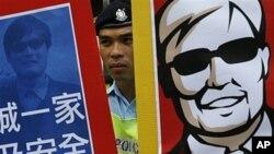 Cảnh sát đứng giữa 2 bức ảnh của nhà hoạt động Trần Quang Thành trong khi biểu tình diễn ra trước văn phòng liên lạc của chính phủ trung ương Trung Quốc ở Hong Kong về việc ông bị ngăn không được gặp các viên chức Mỹ và bạn bè