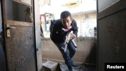 Seorang tentara Laskar Pembebasan Suriah berlari melindungi diri dari tentara pemerintah Suriah di daerah Sheikh Maqsoud di Aleppo, Minggu, 16 Februari 2014.