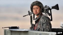 FILE - A South Korean soldier stands on a military guard post near the demilitarized zone (DMZ) dividing the two Koreas in the border city of Paju.