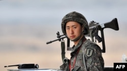 Yon sòlda sid-koreyen monte lagad nan yon pòs militè tou pre zòn demilitarize ki divize 2 Kore yo nan vil Paju, sou fwontyè 2 peyi yo (5 avril 2013).